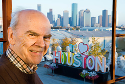 "Portrait of Artist David Adickes with sculpture of ""We Love Houston' with Houston, Texas skyline background."