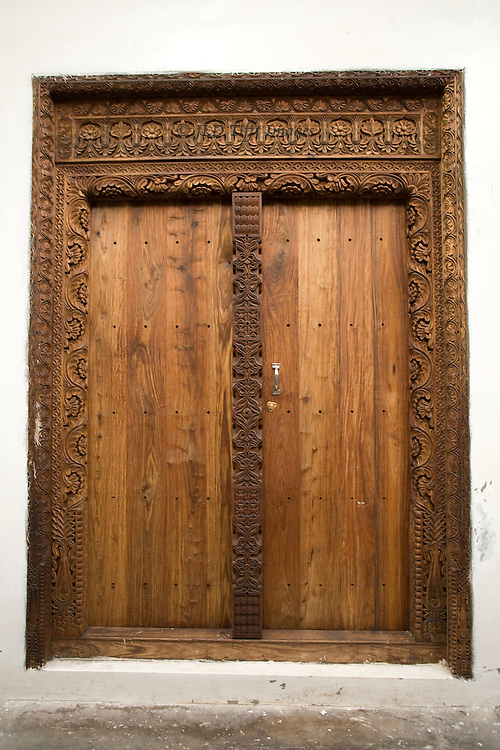 Stonetown wooden door with finely hand carved jambs and architrave and central pillar.  Doors themselves are plain, however.