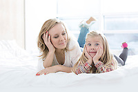 Mother looking at cute daughter making faces while lying in bed
