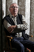 portrait of a 80+ year old man sitting in a chair