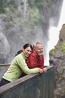Man and woman looking at view near waterfall woman embracing man