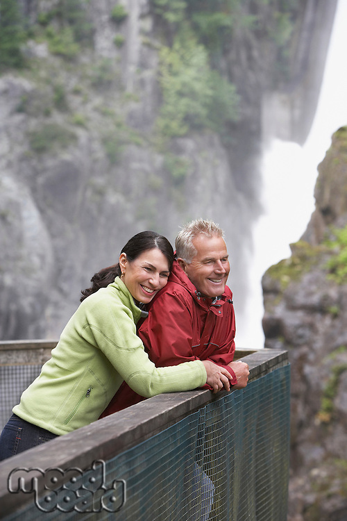 Man and woman looking at view near waterfall woman embracing man
