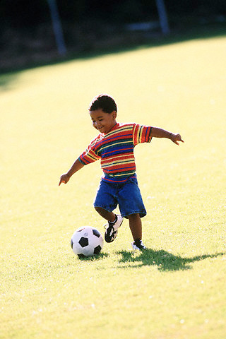 Kid with a soccer ball --- Image by © Jim Cummins/CORBIS