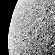 Southern terrain on Saturn's moon Rhea is dimly illuminated by Saturnshine in this Cassini spacecraft view of the dark side of the moon.