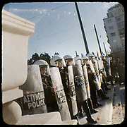 Riot Police pushing back the protesting teenagers to Syntagma square<br /> <br /> Following the murder of a 15 year old boy, Alexandros Grigoropoulos, by a policeman on 6 December 2008 widespread riots, protests and unrest followed lasting for several weeks and spreading beyond the capital and even overseas<br /> <br /> When I walked in the streets of my town the day after the riots I instantly forgot the image I had about Athens, that of a bustling, peaceful, energetic metropolis and in my mind came the old photographs from WWII, the civil war and the students uprising against the dictatorship. <br /> <br /> Thus I decided not to turn my digital camera straight to the destroyed buildings but to photograph through an old camera that worked as a filter, a barrier between me and the city.