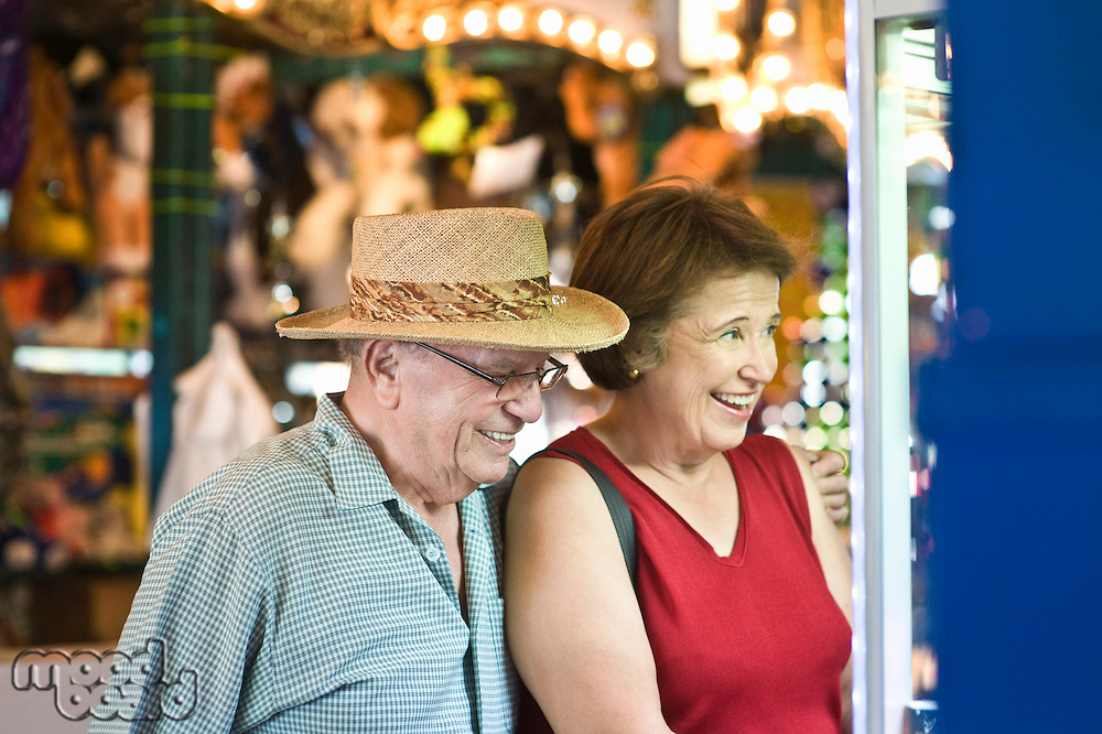 Senior couple watching window display, smiling