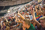 Students participate in an informal survery by holding up their cellphones at First Year Student Convocation.