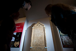 © Licensed to London News Pictures 25/01/2016, Cirencester, UK. Collections officer James Harris (L) looks at a unique Roman tombstone, found in February 2015, here on display for the first time at Corinium Museum in Cirencester. The tombstone was found near skeletal remains thought to belong to the person named on its inscription, making the discovery unique. After being found during excavation works on a former site of a garage, archaeologists said they believed it marked the grave of a 27-year-old woman called Bodica. Other theories point to it possibly belonging to a couple - as skeletal remains of women were found nearby.<br />