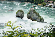 The Rhine Falls (Rheinfall in German) is the largest-volume waterfall in Europe. The falls are on the High Rhine between the municipalities of Neuhausen am Rheinfall and Laufen-Uhwiesen, near the town of Schaffhausen in northern Switzerland, between the cantons of Schaffhausen and Zürich. Rhine Falls are 150 m (450 ft) wide and 23 m (75 ft) high. Winter average water flow is 250 cubic meters per second; while summer averages 700 cubic meters per second. The highest flow ever measured was 1250 cubic meters per second, in 1965; and the lowest, 95 cubic meters per second, in 1921. Rheinfall formed in the last ice age, about 14,000 to 17,000 years ago, by erosion-resistant rocks narrowing the riverbed.
