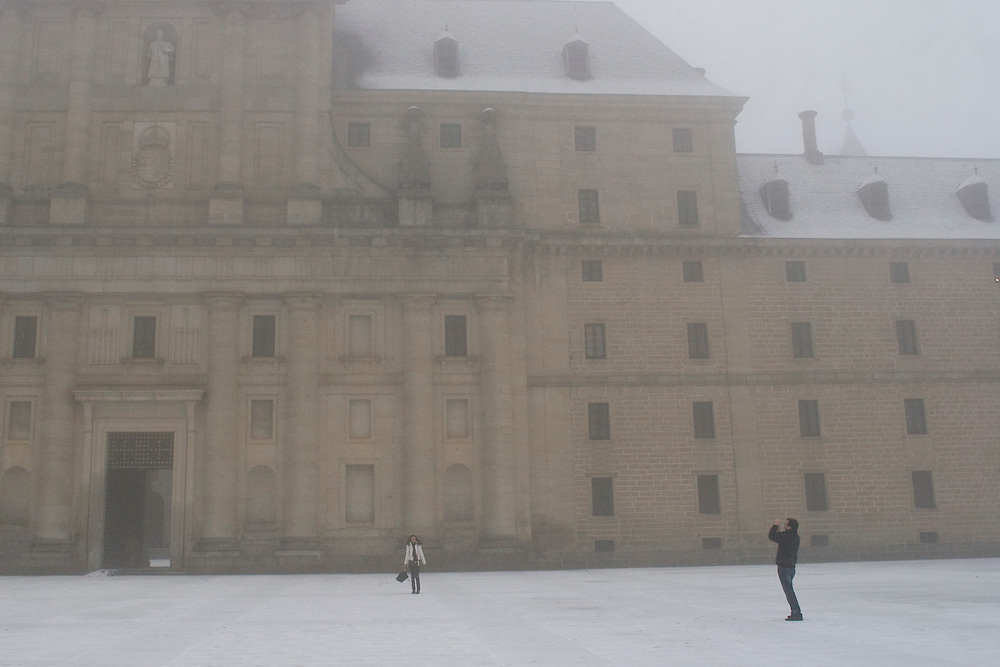 (Robledo de Chavela, Spain - March 4, 2011) - Tourist take photos in front of the monastery as snow falls on a lazy Friday in San Lorenzo de El Escorial outside of Madrid. Photo by Will Nunnally / Will Nunnally Photography