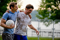 Two muddy soccer players talking off with thier arms around each other