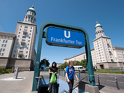 Underground station exit in front of famous East German era Frankfurter Tor buildings with towers on Karl Marx Allee in Berlin Germany