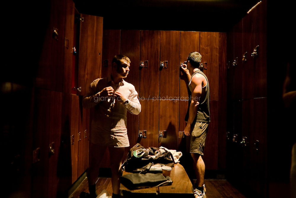 11 December, 2008. New York, NY. Daniel Alexander Osach (or Dan Alex), 24, changes in the locker room of the David Barton Gym in Chelsea, where he works out almost every day after work. Daniel is a gay Go-Go dancer who grew up in New Haven, CT, and moved to New York a year ago. During the day he works for Christopher Hyland, Inc., a high-end fabrics purveyor. At night, he works as a Go-Go dancer in gay and women clubs around New York City. &quot;My life is work, gym, dance and sleep&quot;, Daniela says. Dan has a bachelor in English and majored in Poetry and Economics. After graduation in 2006 he worked as a store manager in a mall for 4 months in Connecticut. Tired and depressed of his job, he went to Florida to relax and then came to New York a year ago. He usually dances at &quot;The Cock&quot;, a  East Village gay bar. &quot;The Cock is not an institution. It's a landmark&quot; Daniel says. Daniel aspires to become maybe a teacher or to work for a travel magazine. &quot;What I would really love to do is to live my life laying down at the beach and reading poetry&quot;<br /> <br /> &copy;2008 Gianni Cipriano for The New York Times<br /> cell. +1 646 465 2168 (USA)<br /> cell. +1 328 567 7923 (Italy)<br /> gianni@giannicipriano.com<br /> www.giannicipriano.com