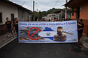 """Members of MUFRAS-32 hold a banner that reads """"We demand a law that prohibits metal mining in El Salvador!"""" as they walk down a street in San Isidro, Cabañas. Pacific Rim's controversial El Dorado gold mine has been the focus of numerous social conflicts at local and national level. Three anti-mining local leaders were murdered in 2009. While a year before, former president Antonio Saca refused to authorize the company's mining permit. This action prompted Pacific Rim to invoked a provision of the Central American Free Trade Agreement (CAFTA) to place the matter in the hands of an international arbitration court. Oceana Gold, who took over Pacific Rim on October 2013 for US $10.2 million , now seeks US $300 million for damages agains the State of El Salvador. San Isidro, Cabañas, El Salvador. September 15, 2014."""