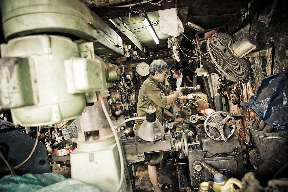 Machinist stays busy in the heat of Hanoi's French Quarter, Vietnam