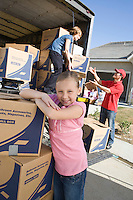 Portrait of girl (7-9) by truck of cardboard boxes