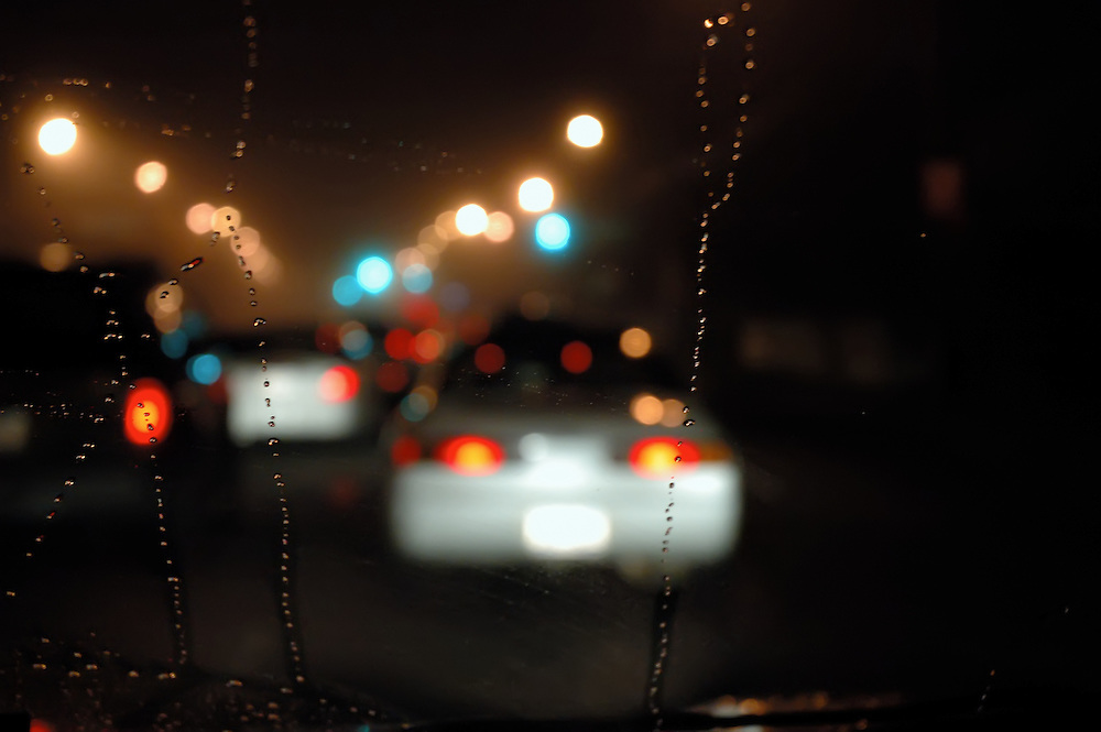 night driving view through windshield with rain trailing down the window