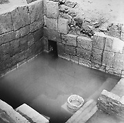 Barbar Temple II, photograph, constructed with cut limestone blocks, containing a sacrificial courtyard, altars, shrines and an underground shrine built around a fresh water spring, seen here, in the Bahrain National Museum, designed by Krohn and Hartvig Rasmussen, inaugurated December 1988 by Amir Shaikh Isa Bin Salman Al-Khalifa, in Manama, Bahrain. This large temple was discovered near the village of Barbar and the site consists of 3 successive temples, with the 2 oldest temples terraced with a central platform above an outer oval platform, in Sumerian style. The Bahrain National Museum houses cultural and archaeological collections covering 6000 years of history, with rooms entitled Burial Mounds, Dilmun, Tylos and Islam, Customs and Traditions, Traditional Trades and Crafts, and Documents and Manuscripts. Picture by Manuel Cohen