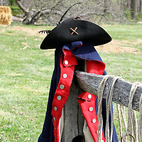 An American Revolution Continental Army jacket and hat resting on a fence post in Jockey Hollow National Park, New Jersey, USA. The Continental Army wintered in Jockey Hollow in 1779-1782. The uniform is part of a re-enactment in the Park.