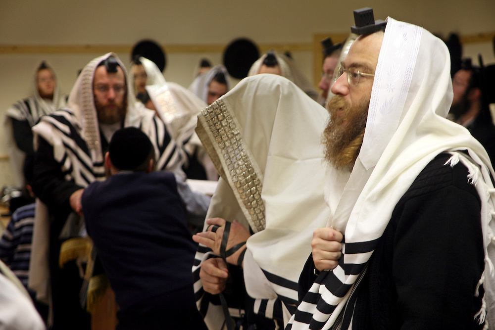 Orthodox Jewish men belonging the Bobov Hasidism during Morning Prayer inside a Stamford Hill synagogue. Communal praying in a minyan (quorum) is preferred by men who wear a Tallit (prayer shawl) and a Tefillin (a box containing strips of parchment inscribed with 4 passages of the Torah) on their heads with the leather straps around their arm and hand.