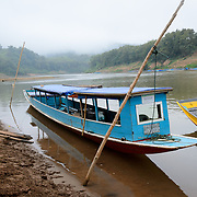 Fast passenger boats moored against the banks of the Nam Ou (River Ou) in Nong Khiaw in norther Laos.