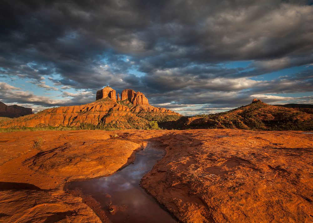 Last rays of warm light illuminate Cahedral Rocks as storm clouds break up, Sedona, Arizona
