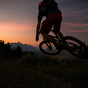 Andrew Whiteford gets some air along the ridge of the Ferrin's Singletrack just after sunset above the town of Jackson with the Teton Range in the distance.