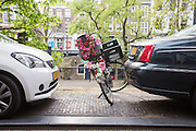 In Utrecht staat een met bloemen versierde fiets geparkeerd tussen twee auto's op de Oudegracht.<br /> <br /> In Utrecht a bike decorated with flowers is parked between two cars.