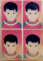 Detail of passport photographs of Chinese boy in photographer s shop window in China