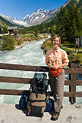 "Carol arrives with rolling luggage at a bridge over the Lonza River in Blatten, Loetschental, in the Valais canton of Switzerland, the Alps, Europe. UNESCO lists ""Swiss Alps Jungfrau-Aletsch"" as a World Heritage Area (2001, 2007). For licensing options, please inquire."