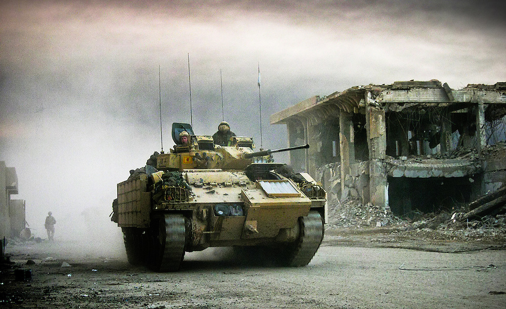 A British Warrior armoured vehicle from the Black Watch regiment, part of the Desert Rats (7th Armoured Brigade), returns to a bombed out compound on the outskirts of the southern Iraqi city of Basra, March 2003. The vehicle and several others had just completed a raid into the city, which was still in Iraqi hands.