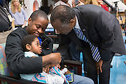 Retired Neurosurgeon and Republican presidential candidate Dr. Ben Carson greets 2-year-old Aiden Rennis held by his father Roxroy Rennis during a visit to the MUSC Children's Hospital December 22, 2015 in Charleston, South Carolina. Aiden suffers from a rare form of brain inflammation and is a patient at the hospital.