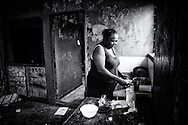 Anne Olby preparing some instant noodles in a condemned house in Kennedy Hill. A lack of affordable short-term accommodation, combined with Aboriginal people moving in from remote communities, has led to people camping on bush blocks, parks in town and abounded buildings.<br />This house was demolished on September 22th 2014. Now people are squatting outside the fence in the sand dunes of Kennedy Hill. Broome, Western Australia. &copy;Ingetje Tadros/Diimex