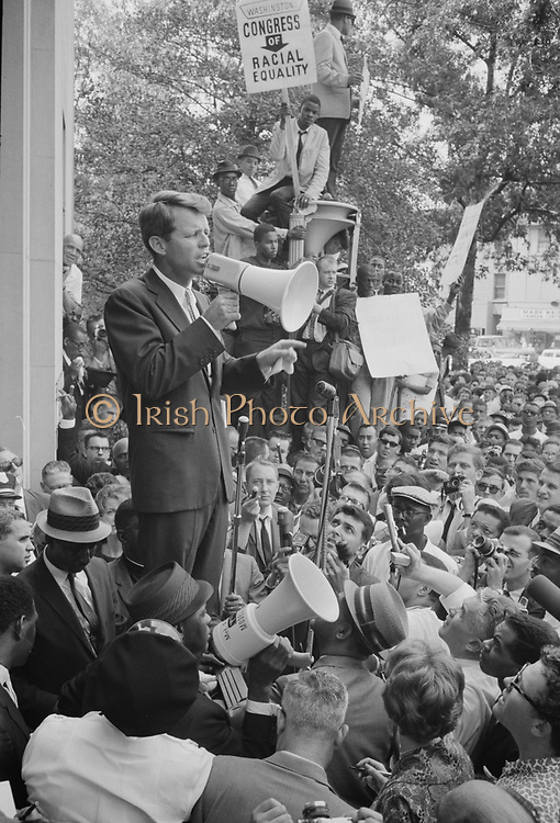 Photograph showing Attorney General Robert F Kennedy speaking to a crowd of African Americans and whites through a megaphone outside the Justice Department; sign for Congress of Racial Equality is prominently displayed. 1963 June 14.  Photographer:  Warren K Leffler.