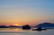 Sunset and islets on the Inside Passage, near Ward Cove, Revillagigedo Island; Ketchikan, Alaska.