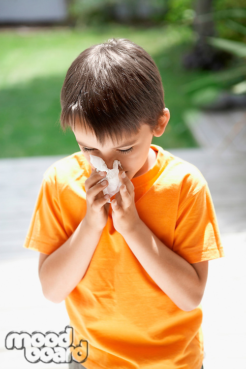 Little Boy Blowing His Nose in back yard