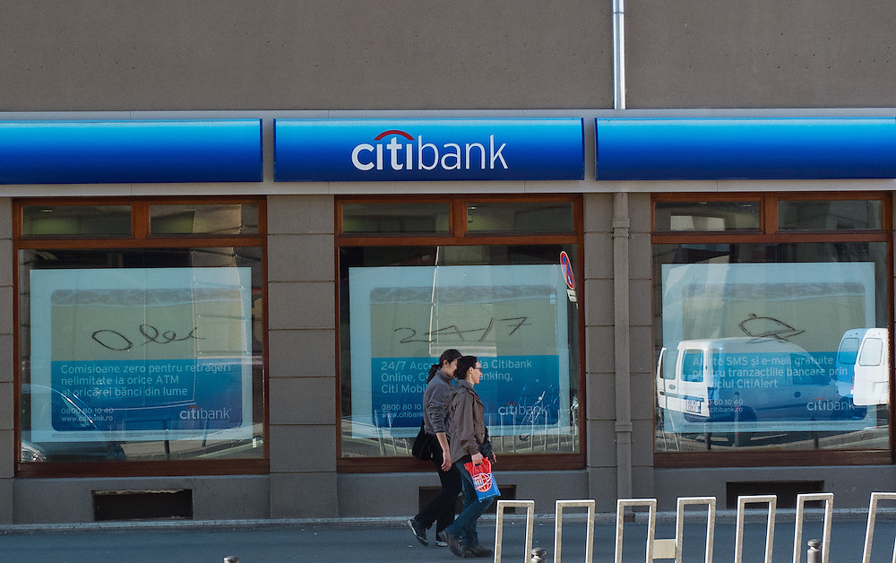 TIMISOARA, ROMANIA - APRIL 21:  Two women walk in front of a Citi Bank in the city centre on April 21, 2013 in Timisoara, Romania.  Romania has abandoned a target deadline of 2015 to switch to the single European currency and will now submit to the European Commission a programme on progress towards the adoption of the Euro, which for the first time will not have a target date. (Photo by Marco Secchi/Getty Images)