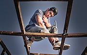 Joven rapero retratado sobre una estructura vieja de metal, en el muelle Portales, Valparaíso, Chile.