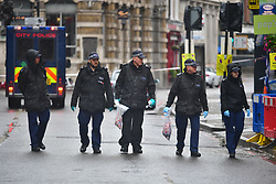 © Licensed to London News Pictures. 06/06/2017. London, UK.       Members off a police search team carry out finger tip searches on roads surrounding Borough Market, following a terrorist attack in Saturday evening.   Three men attacked members of the public  after a white van rammed pedestrians on London Bridge.   Ten people including the three suspected attackers were killed and 48 injured in the attack. Photo credit: Ben Cawthra/LNP