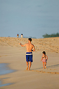 A father and daughter walk along the beach on the North Shore of Oahu, Hawaii.