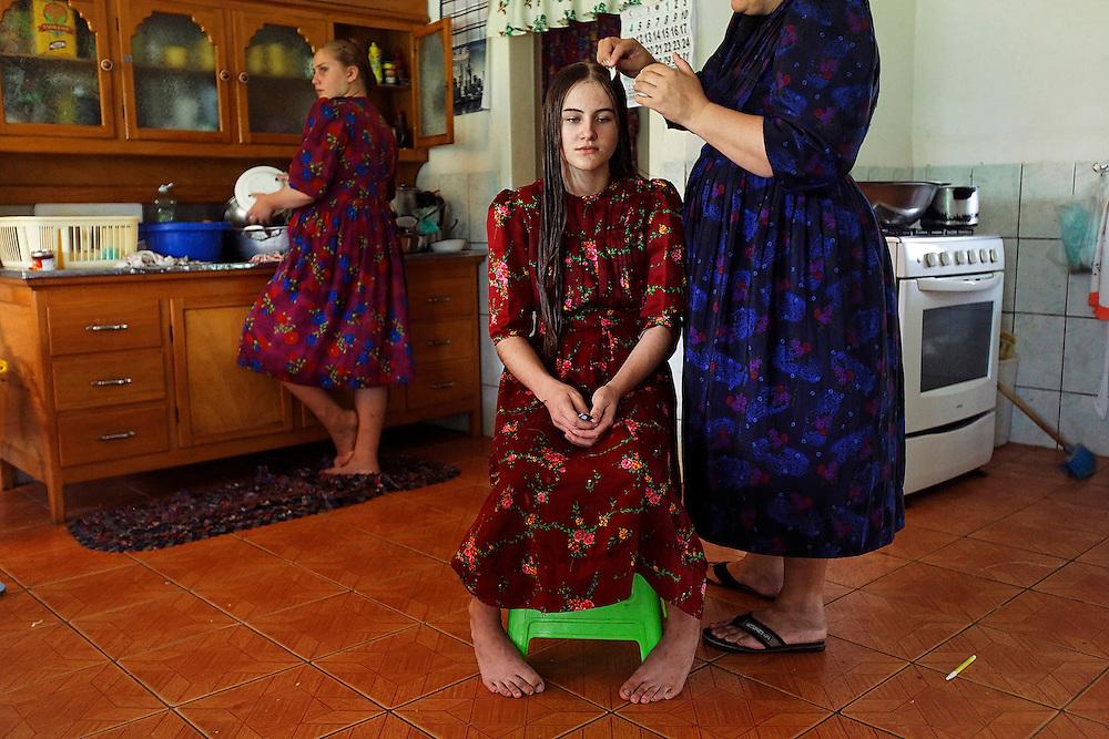 Anna Rempel gets her hair braided at home.  Mennonite women never cut their hair throughout their lifes.