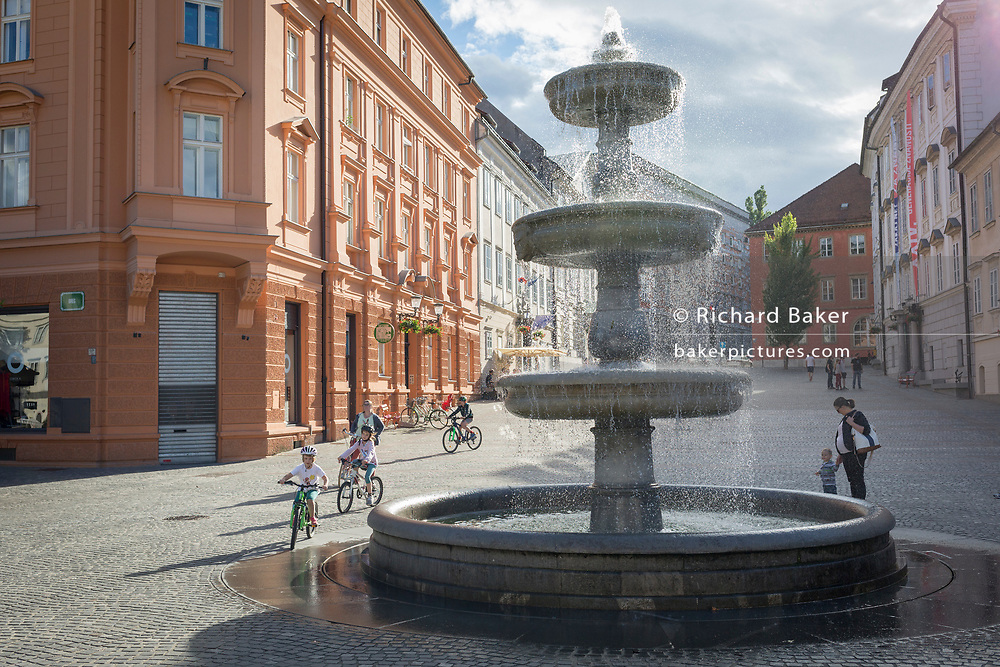 Children cycle in circles around the fountain on Novi Square in the Slovenian capital, Ljubljana, on 25th June 2018, in Ljubljana, Slovenia.