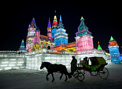 Horse and carriage with large illuminated building sculpture at night at the annual Harbin Ice Lantern festival in 2009