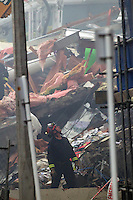 A rescue worker surveys the damage of the CTV building in the centre of Christchurch as rescue workers search the rubble for survivors after a Powerful earth quack ripped through Christchurch, New Zealand on Tuesday lunch time killing at least 65 people as it brought down buildings, buckled roads and damaged churches and the Cities Cathedral. Photo Tim Clayton