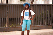 SMILING TEENAGE BLACK GIRL IN BLUE COWBOY HAR AND BLUE JEANS RIO