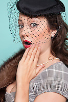 Portrait of shocked young woman wearing veiled hat and fur boa against blue background