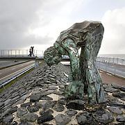 """Nederland Den Oever Zurich 22 november 2008 20081122 Foto: David Rozing ..Serie afsluitdijk. De Afsluitdijk is een belangrijke waterkering en verkeersweg in Nederland. De waterkering sluit het IJsselmeer af van de Waddenzee. Hieraan ontleent de dijk zijn naam. De verkeersweg, onderdeel van Rijksweg a7, verbindt Noord-Holland met Friesland...afsluitdijk ter hoogte van de uitkijktoren. Bronzen beeld Steenzetter.Ter gelegenheid van 50 jaar Afsluitdijk werd in 1982 het beeld de """"Steenzetter"""" van Ineke van Dijk geplaatst. Tekst: """" de strijd tegen het water blijft een strijd door en voor de mens """" standbeeld, monument, mensen, bezoekers deltaplan...Foto David Rozing"""