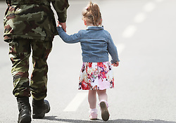 Private Daniel Crofton holds the hand of his daughter Amber Kelly Crofton, 3, at Custume Barracks, Athlone, following a review of the 110th Infantry Battalion ahead of their six-month deployment to South Lebanon as part of United Nations Interim Force in Lebanon (Unifil).