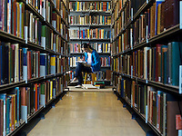 Young woman reading by bookshelf in library