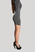 Side view of sensuous woman wearing dress against gray background
